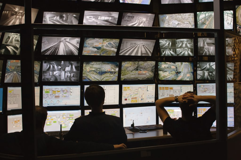 Three security personnel monitoring camera activity